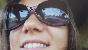La mujer joven feliz lleva las gafas de sol que se sientan en el pasajero del coche que mira hacia fuera la ventana el día solead Fotografía de archivo libre de regalías