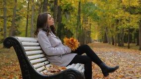 La mujer joven feliz mira las hojas que caen, y agita a su miel almacen de metraje de vídeo