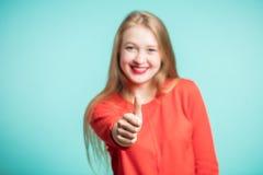 La mujer joven feliz muestra los pulgares para arriba en un fondo azul, finger en foco Cierre para arriba Imagen de archivo libre de regalías