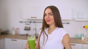 La mujer joven feliz que bebe el jugo verde fresco que goza del detox limpia La hembra apta está disfrutando de la bebida sana en almacen de metraje de vídeo