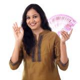 La mujer joven feliz que detiene al indio 2000 rupias observa p Fotos de archivo