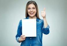 La mujer joven feliz que lleva a cabo el tablero de la muestra muestra el pulgar para arriba Imagen de archivo libre de regalías