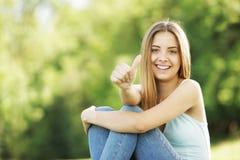 La mujer joven feliz que muestra los pulgares sube la muestra Fotografía de archivo