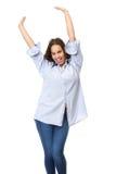 La mujer joven feliz que se colocaba con las manos aumentó en la celebración Foto de archivo