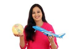 La mujer joven feliz que sostiene el globo y el juguete acepillan contra blanco imágenes de archivo libres de regalías