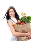 La mujer joven feliz que sostiene un panier lleno de ultramarinos da fruto Fotos de archivo libres de regalías