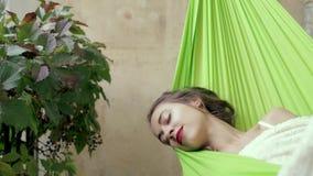 La mujer joven feliz relajó mentiras en una hamaca en la casa del balcón La mujer toma el sol y toma el sol en una hamaca almacen de metraje de vídeo
