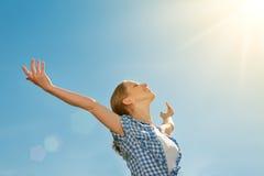 La mujer joven feliz se abre los brazos en el cielo Foto de archivo libre de regalías