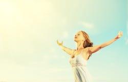 La mujer joven feliz se abre los brazos en el cielo Imagen de archivo libre de regalías