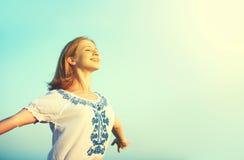La mujer joven feliz se abre los brazos en el cielo Foto de archivo