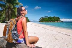 La mujer joven feliz se sienta con la mochila en el mar de la costa y la mirada a imagen de archivo