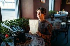 La mujer joven feliz se sienta por la tabla en café imágenes de archivo libres de regalías