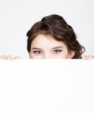 La mujer joven feliz sonriente que se coloca detrás y que se inclina en una cartelera o un cartel en blanco blanca, expresa difer Foto de archivo libre de regalías