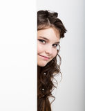 La mujer joven feliz sonriente que se coloca detrás y que se inclina en una cartelera o un cartel en blanco blanca, expresa difer Fotografía de archivo