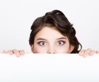 La mujer joven feliz sonriente que se coloca detrás y que se inclina en una cartelera o un cartel en blanco blanca, expresa difer Fotos de archivo libres de regalías