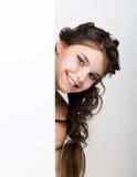 La mujer joven feliz sonriente que se coloca detrás y que se inclina en una cartelera o un cartel en blanco blanca, expresa difer Fotografía de archivo libre de regalías