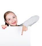 La mujer joven feliz sonriente que se coloca detrás y que se inclina en una cartelera o un cartel en blanco blanca, expresa difer Imagen de archivo