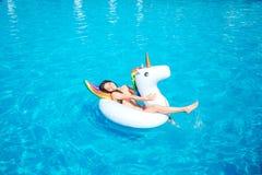 La mujer joven feliz y positiva está mintiendo en el colchón de aire en el medio de piscina Ella agita con la fabricación de la p fotos de archivo