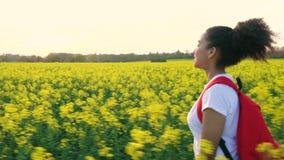 La mujer joven femenina del adolescente afroamericano de la muchacha que camina con la mochila roja en el campo del amarillo de l almacen de video