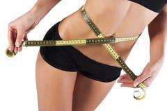 La mujer joven fina mide la cintura Imagen de archivo