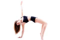 La mujer joven flexible hace ejercicios atléticos, gimnásticos aislada en el fondo blanco Fotos de archivo libres de regalías