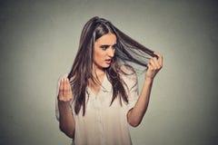 La mujer joven frustrada infeliz la sorprendió es pelo perdidoso imagenes de archivo