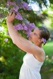 La mujer joven goza de la lila floreciente foto de archivo libre de regalías