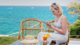 La mujer joven goza de la tableta El sentarse en el café de la terraza del verano que pasa por alto el mar almacen de video