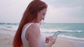 La mujer joven goza de un smartphone en una playa tropical almacen de video