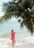La mujer joven goza del cóctel del coco en la playa Foto de archivo libre de regalías