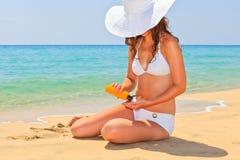 La mujer joven goza del sol en la playa Imagen de archivo