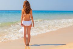 La mujer joven goza del sol en la playa Fotos de archivo libres de regalías