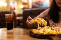 La mujer joven goza el comer de la pizza hawaiana con el refresco en resta imágenes de archivo libres de regalías