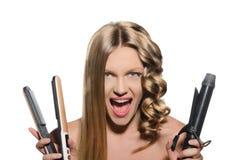La mujer joven guarda los bigudíes y el rectificador de pelo Fotos de archivo