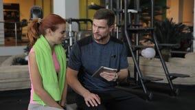 La mujer joven habla con el instructor de sexo masculino en el club de deportes dentro almacen de metraje de vídeo