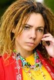 La mujer joven habla en el teléfono con los dreadlocks Fotografía de archivo