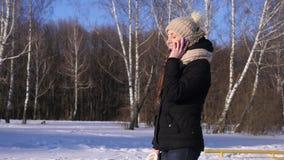 La mujer joven habla en el teléfono en el parque del invierno, cámara lenta almacen de metraje de vídeo