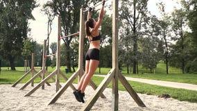La mujer joven hace diversos ejercicios del peso del cuerpo en la barra horizontal almacen de video