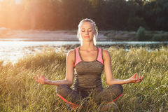La mujer joven hace ejercicios de la yoga Fotografía de archivo