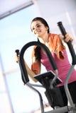 La mujer joven hace ejercicios en el elipsoide Imagen de archivo