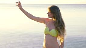 La mujer joven hace el selfie cerca del mar HD metrajes
