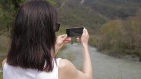 La mujer joven hace la foto de paisaje del r?o de la monta?a en c?mara del smartphone, para compartir en medios sociales de Inter almacen de video