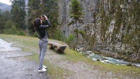 La mujer joven hace la foto de paisaje del r?o de la monta?a en c?mara del smartphone, para compartir en medios sociales de Inter metrajes