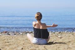 La mujer joven hace la meditación en actitud del loto en el mar/la playa, la armonía y la reflexión del océano Yoga practicante d Fotografía de archivo libre de regalías