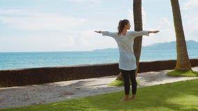 La mujer joven hace práctica de la yoga en la playa cerca del océano tranquilo en la isla Bali con el fondo hermoso almacen de video