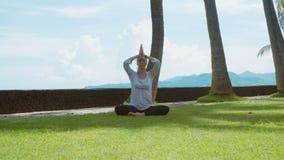 La mujer joven hace la práctica de la yoga, relajándose en actitud del loto en la playa del océano en la isla Bali, el fondo herm