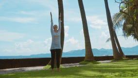 La mujer joven hace la práctica de la yoga, relajándose y estirando en la playa cerca del océano tranquilo en la isla Bali con el
