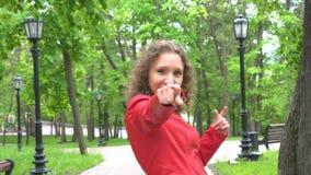 La mujer joven hace que las rocas o ILY o los cuernos del diablo firman por ambas manos a la cámara almacen de video