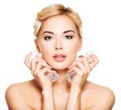 La mujer joven hermosa aplica el hielo a la cara Imagen de archivo libre de regalías