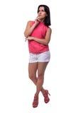 La mujer joven hermosa, atractiva en blusa y el cortocircuito pone en cortocircuito el pensamiento, poniendo un finger para hacer Foto de archivo libre de regalías
